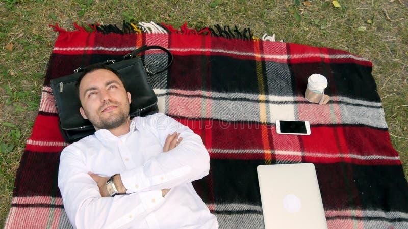 Homme d'affaires moderne et détente avec des mains derrière la tête sur l'herbe avec l'ordinateur portable tout près photographie stock
