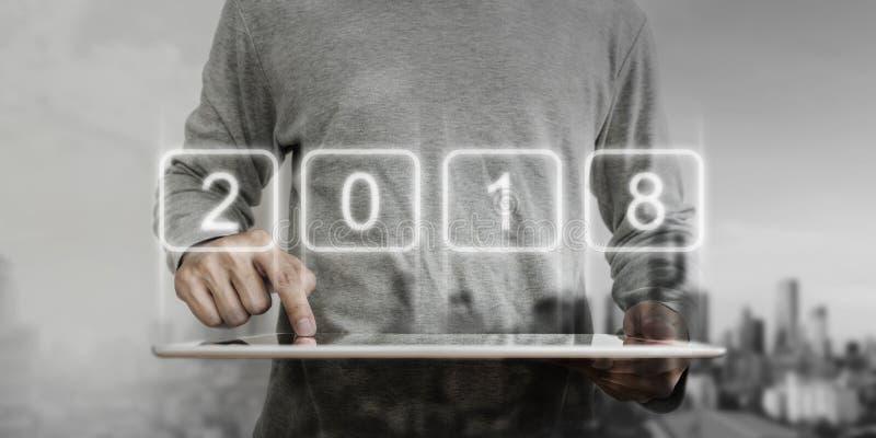 Homme d'affaires moderne se dirigeant sur le comprimé numérique avec l'hologramme 2018 Nouvelle année, nouvelle technologie et no photographie stock