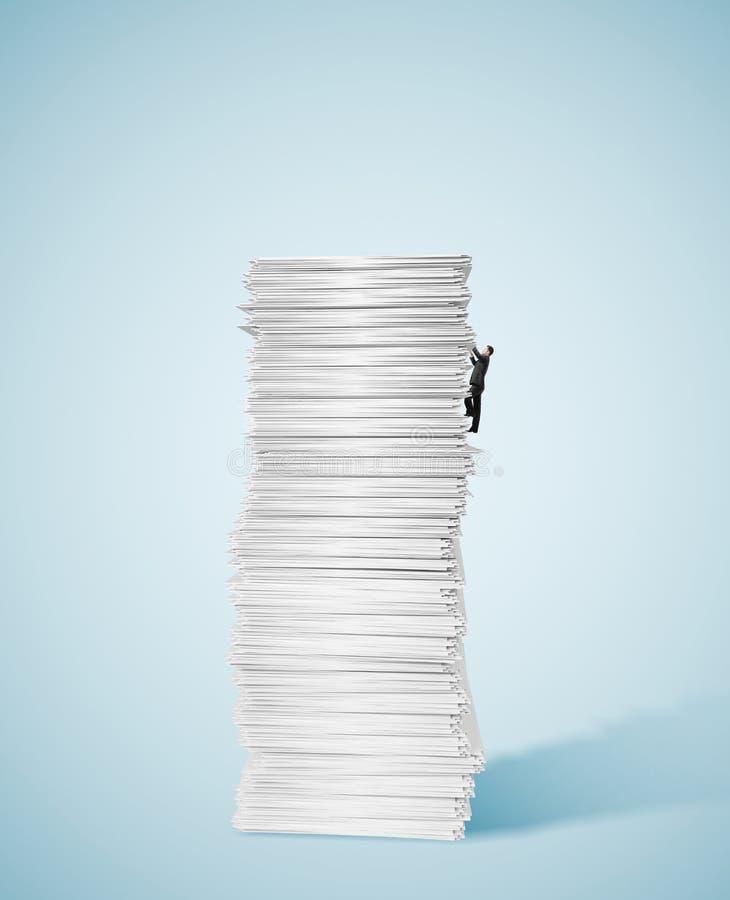 Homme d'affaires montant une grande pile énorme de papier photographie stock libre de droits