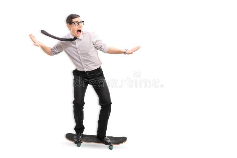 Homme d'affaires montant une planche à roulettes rapidement photographie stock