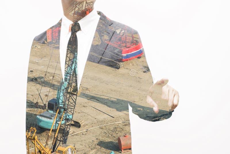 Homme d'affaires montrant le composé de main et de doigt avec la construction photographie stock libre de droits