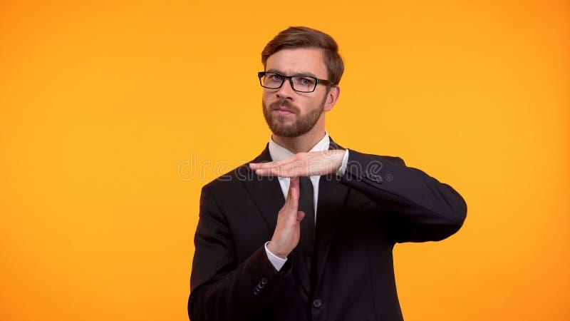 Homme d'affaires montrant le geste de temporisation, d'isolement sur la date-butoir orange de fond images stock