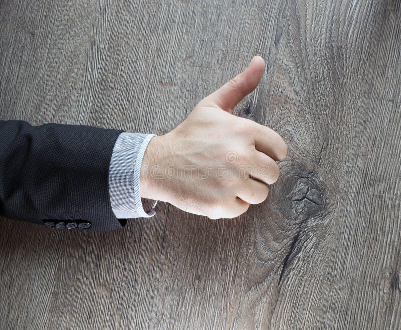 Homme d'affaires montrant le signe CORRECT avec son pouce d'isolement avec le fond en bois foncé affaire d'affaires de succès Hom photographie stock libre de droits