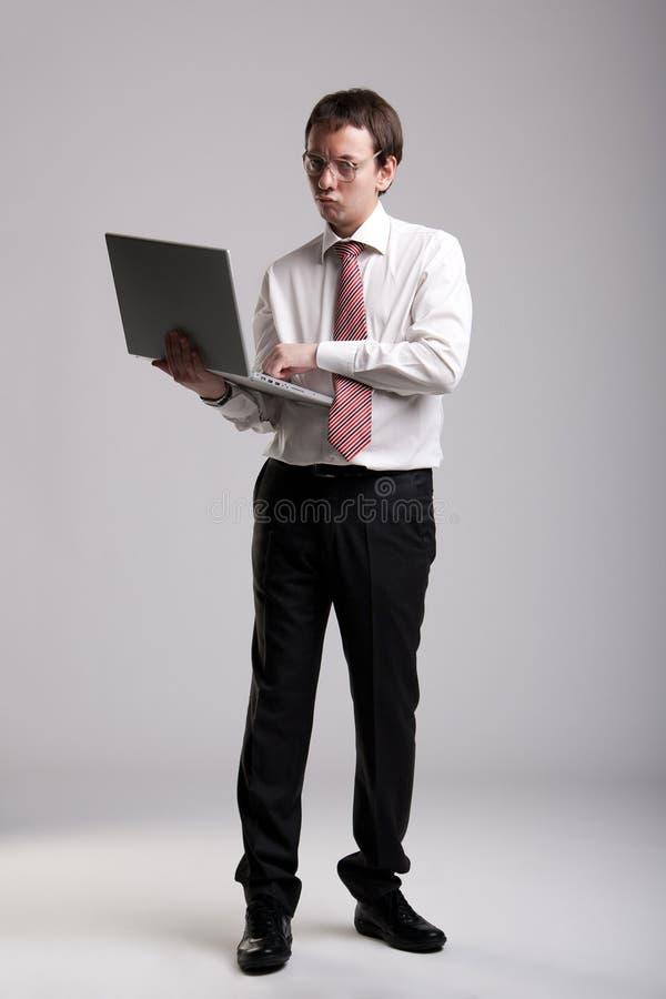 Homme d'affaires Nerdy retenant un ordinateur portatif image libre de droits