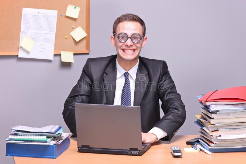 Homme d'affaires Nerdy travaillant sur un ordinateur portatif photographie stock