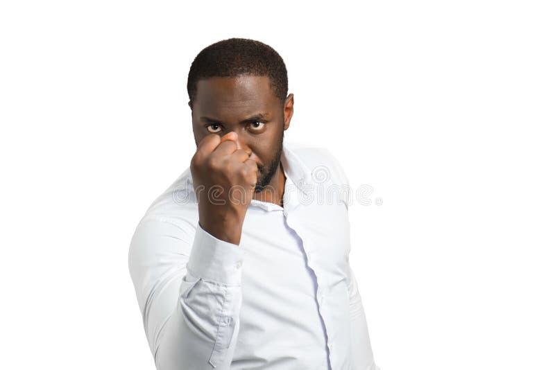 Homme d'affaires noir agressif secouant le poing image stock