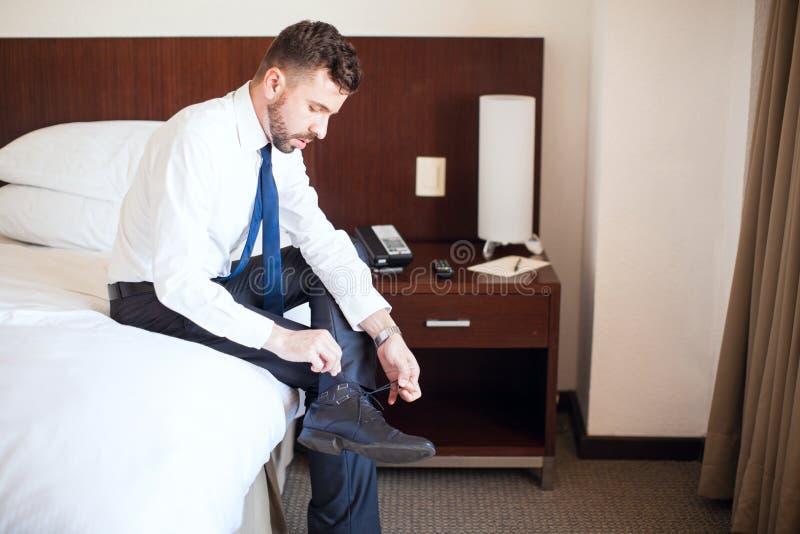 Homme d'affaires obtenant habillé dans un hôtel image stock