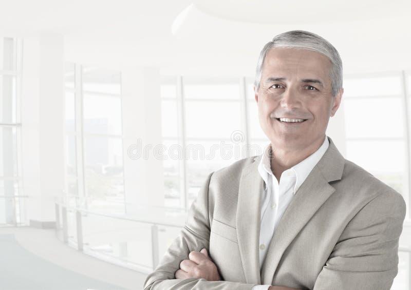 Homme d'affaires occasionnel dans un bureau moderne avec ses bras pliés images libres de droits