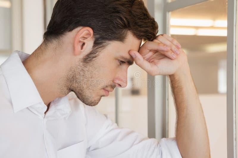 Homme d'affaires occasionnel se penchant sur la fenêtre semblant inquiétée images stock