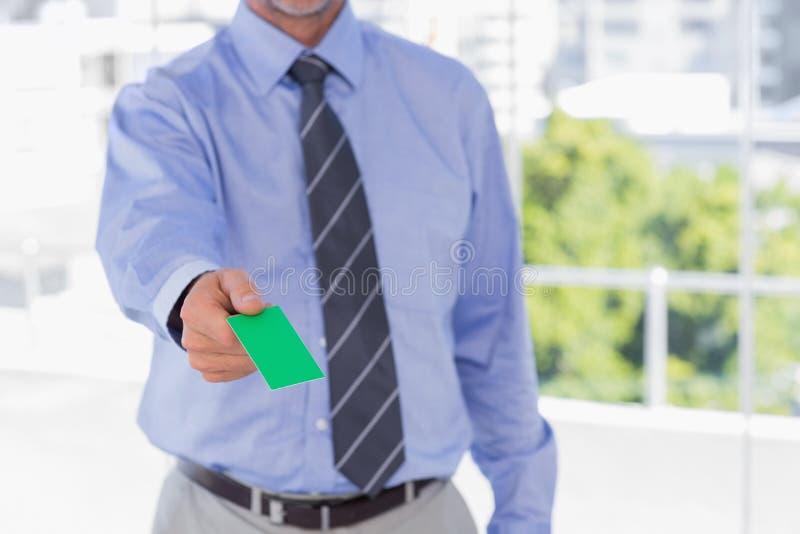 Homme d'affaires offrant la carte de visite professionnelle de visite verte images stock