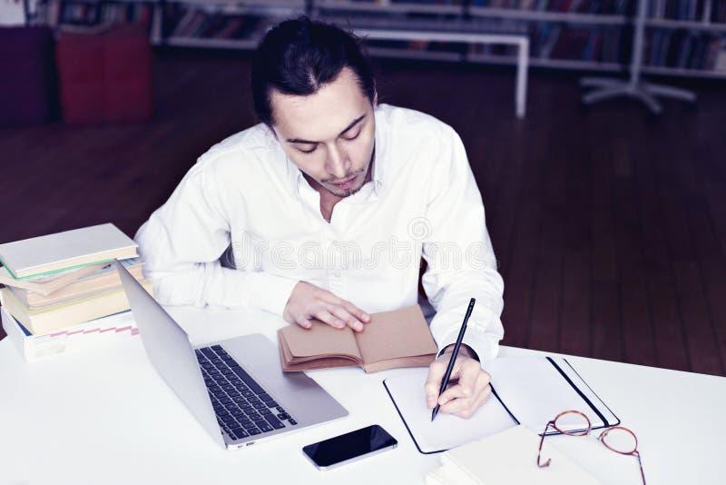 Homme d'affaires ou sourire d'étudiant, travaillant sur l'ordinateur portable lisant un livre dans une bibliothèque photos stock
