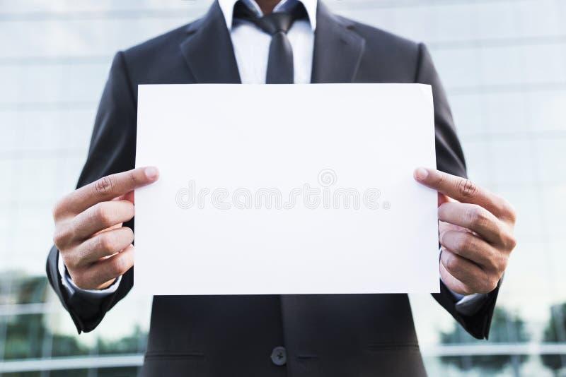 Homme d'affaires ou travailleur anonyme se tenant dans le costume avec le papier image libre de droits