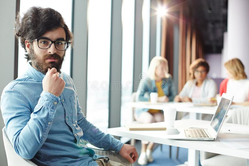 Homme d'affaires par le lieu de travail photo stock
