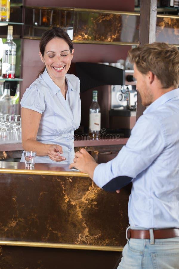 Homme d'affaires parlant à la barmaid dans la barre photographie stock libre de droits