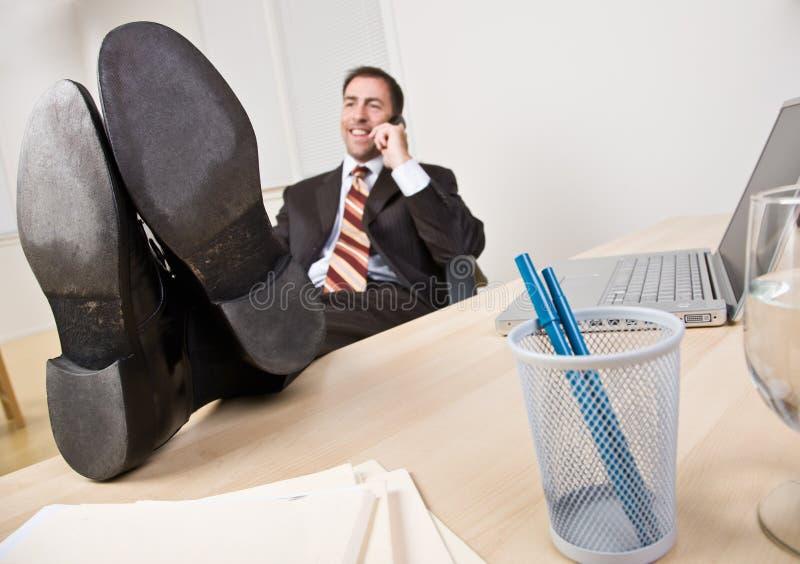 Homme d'affaires parlant au téléphone avec des pieds vers le haut photographie stock