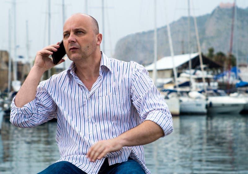 Homme d'affaires parlant au téléphone près du port luxueux images stock