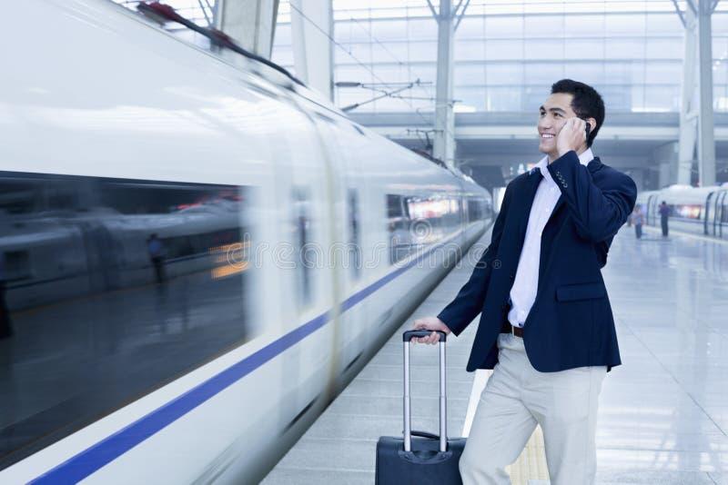 Homme d'affaires parlant au téléphone sur la plate-forme de chemin de fer en un train à grande vitesse dans Pékin image stock