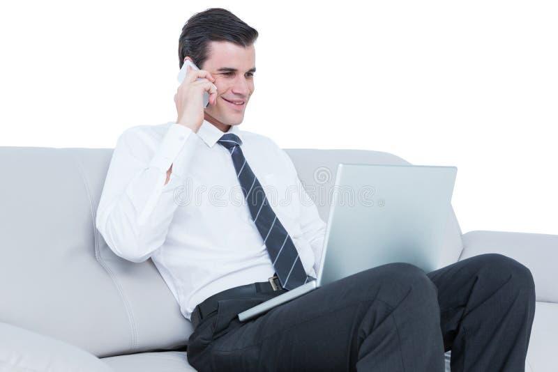 homme d'affaires parlant au téléphone sur le sofa avec son ordinateur portable photographie stock libre de droits