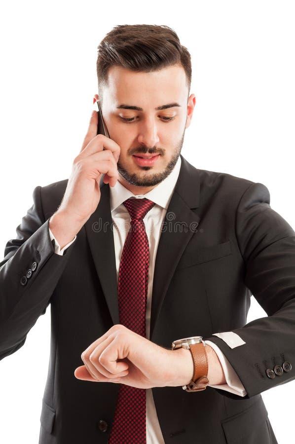 Homme d'affaires parlant au téléphone tout en vérifiant sa montre photographie stock libre de droits