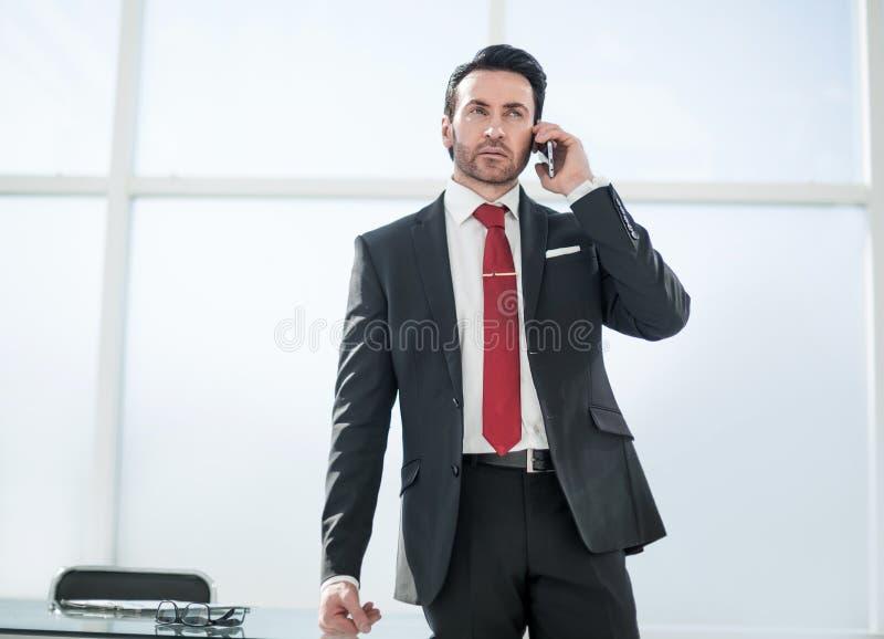 Homme d'affaires parlant sur la position de téléphone portable dans le bureau images stock
