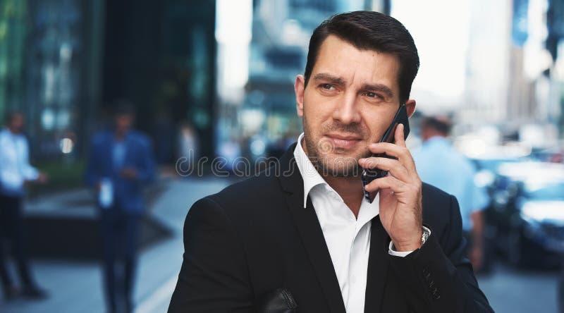 Homme d'affaires parlant sur le smartphone dedans en centre ville photo libre de droits
