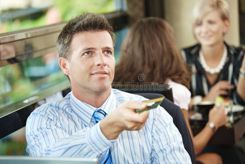 Homme d'affaires payant en café images stock