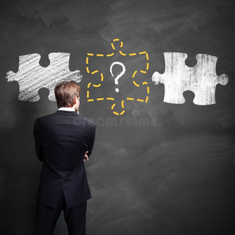 Homme d'affaires pensant à un morceau absent d'un puzzle image libre de droits