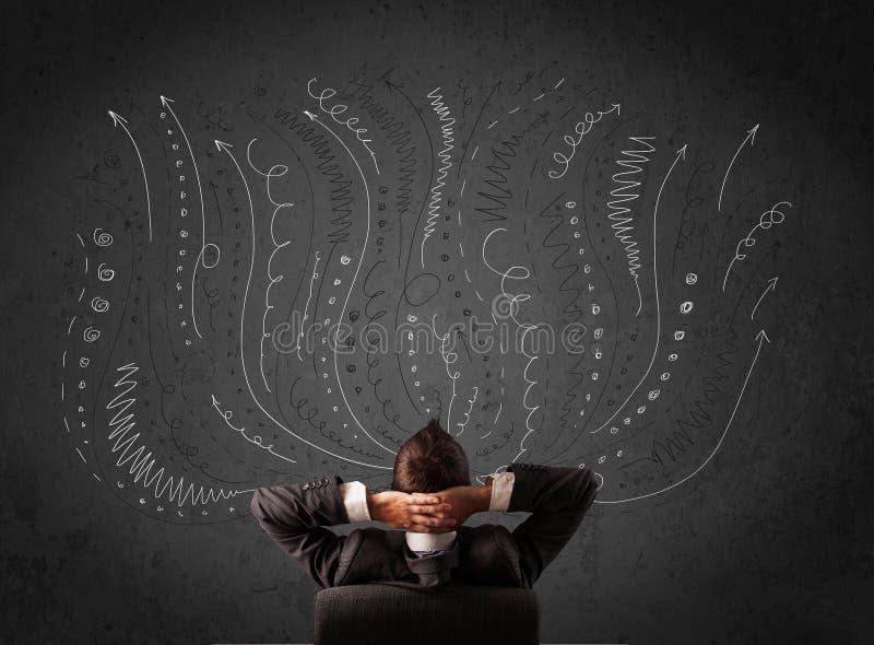 Homme d'affaires pensant avec les flèches esquissées devant un chalkboa photos stock