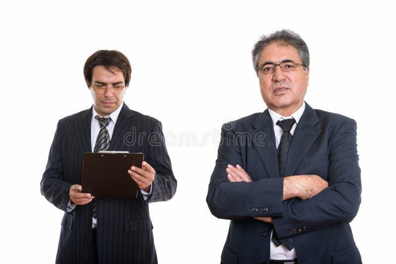 Homme d'affaires persan supérieur avec les bras croisés et le jeune Persan b image stock