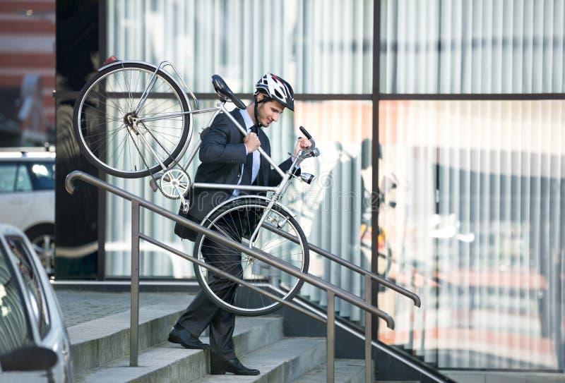 Homme d'affaires portant son vélo photographie stock libre de droits