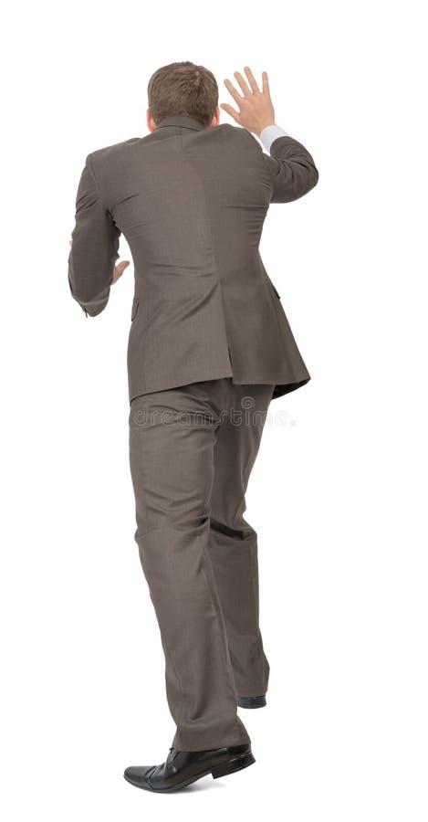 Homme d'affaires poussant l'espace vide, vue arrière photos stock