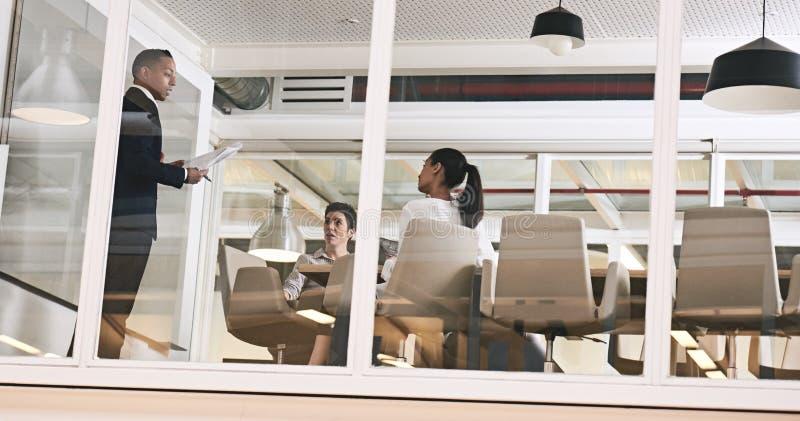 Homme d'affaires présentant un exposé dans le bureau moderne avec des murs de verre image stock