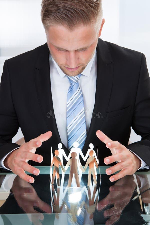 Homme d'affaires prenant soin des personnes de papier photographie stock