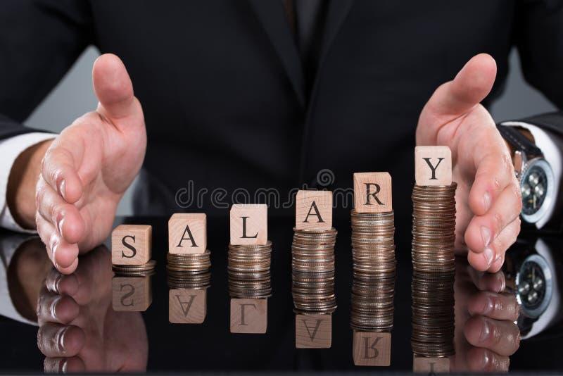 Homme d'affaires Protecting Salary Blocks sur les pièces de monnaie empilées photo libre de droits