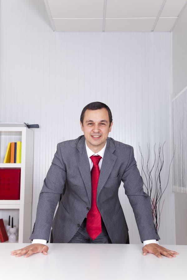 Homme d'affaires puissant au bureau photos stock