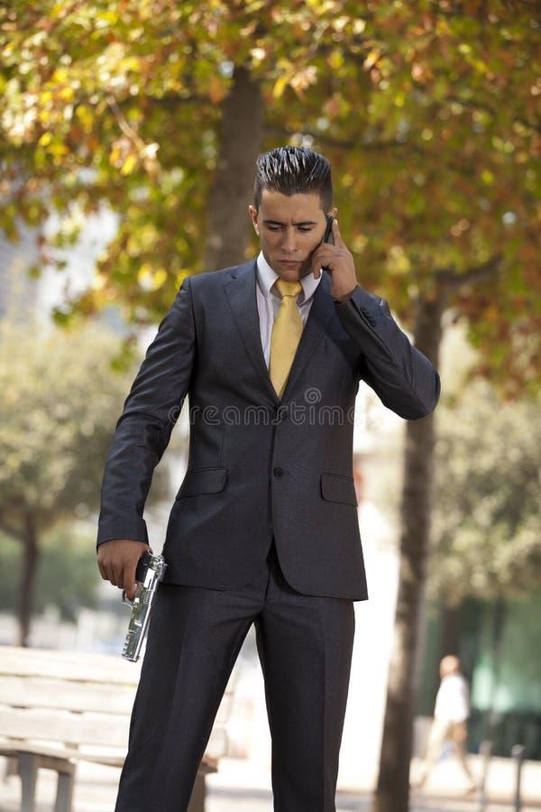 Homme d'affaires puissant de garantie parlant à son portable avec un ha images stock