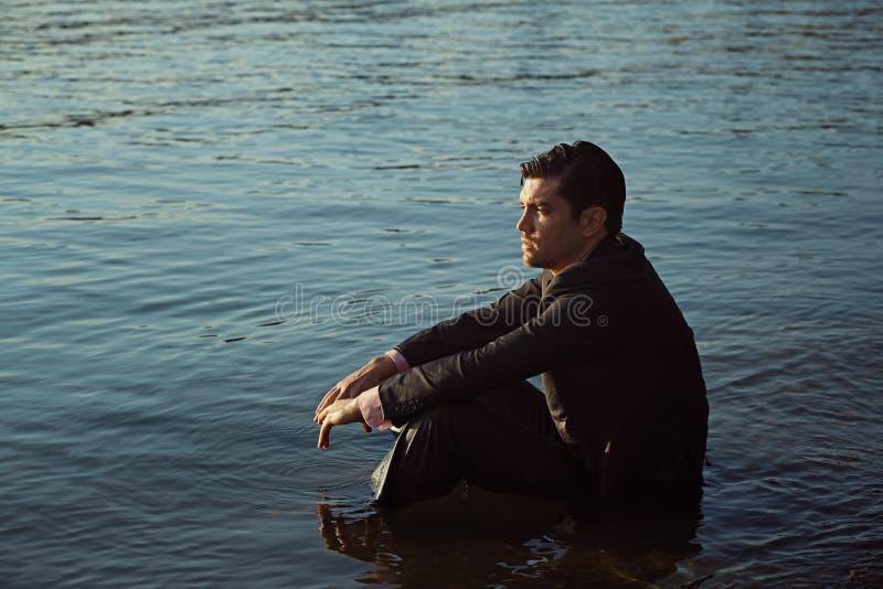 Homme d'affaires réfléchi assis sur un rivage de lac photographie stock