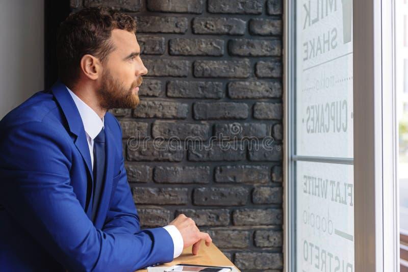 Homme d'affaires réfléchi dans un costume se reposant à l'intérieur photo stock
