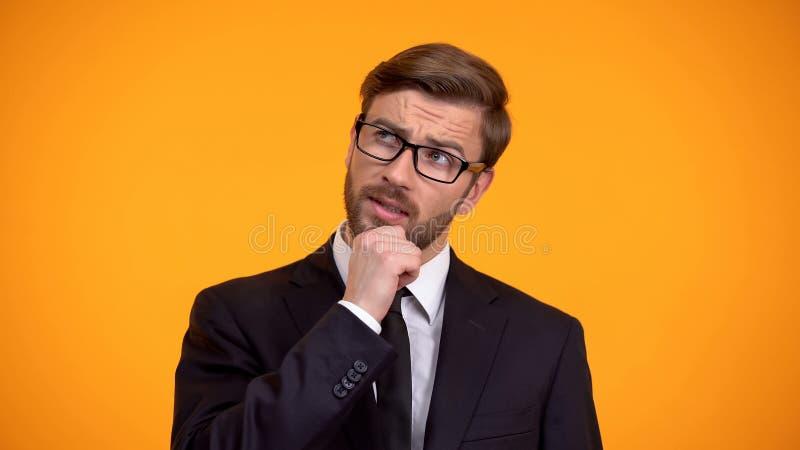 Homme d'affaires r?fl?chi pensant aux id?es pour le d?but, fond orange photos stock