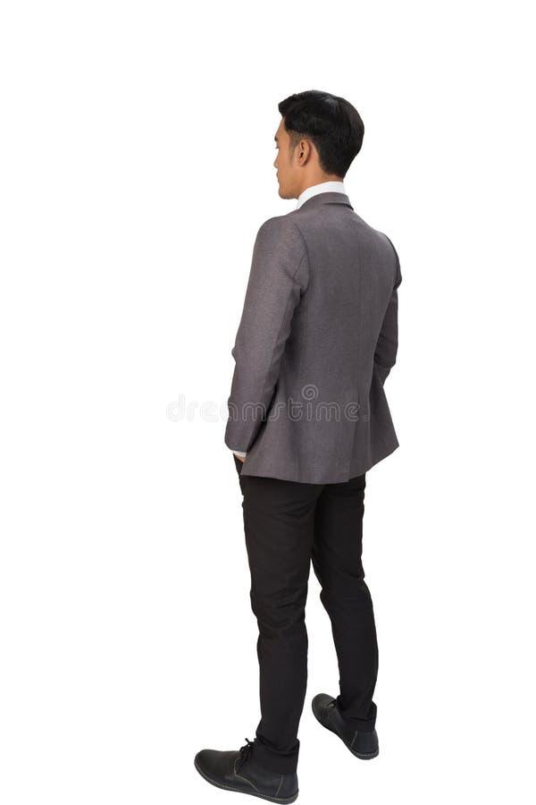 Homme d'affaires réfléchi se tenant de nouveau à l'appareil-photo sur le backgrou blanc photo stock
