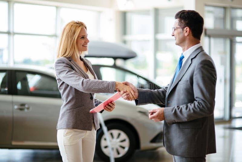 Homme d'affaires réussi à un concessionnaire automobile - vente des véhicules aux clients images libres de droits