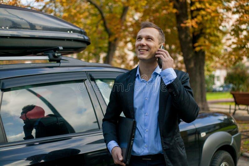 Homme d'affaires réussi dans le costume avec l'ordinateur portable dans la ville photos stock