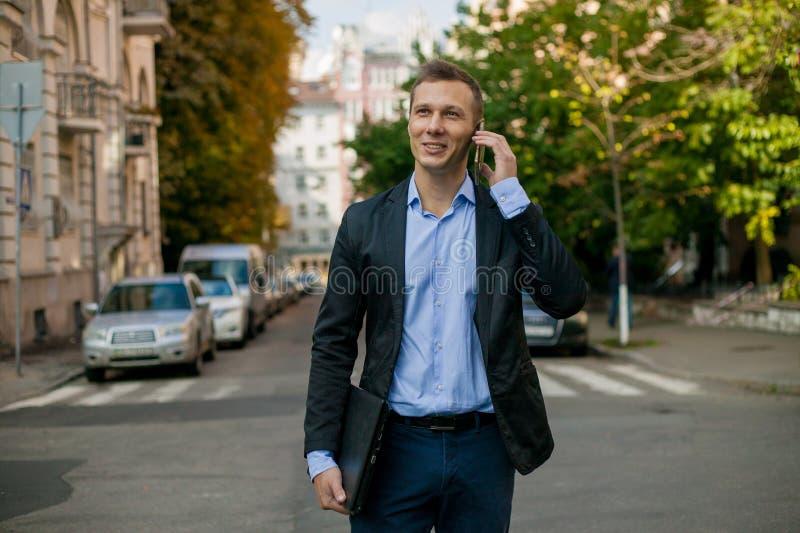 Homme d'affaires réussi dans le costume avec l'ordinateur portable dans la ville photo stock