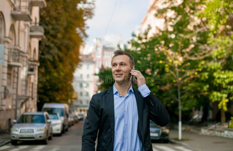 Homme d'affaires réussi dans le costume avec l'ordinateur portable dans la ville photographie stock