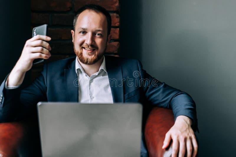 Homme d'affaires réussi dans le costume se reposant dans une chaise avec un ordinateur portable, tenant un smartphone dans sa mai image stock