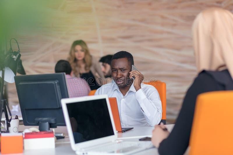 Homme d'affaires réussi de sourire heureux d'Afro-américain dedans dans un bureau de démarrage lumineux moderne à l'intérieur photos stock