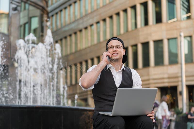 Homme d'affaires réussi heureux travaillant avec l'ordinateur portable et le téléphone dehors photographie stock