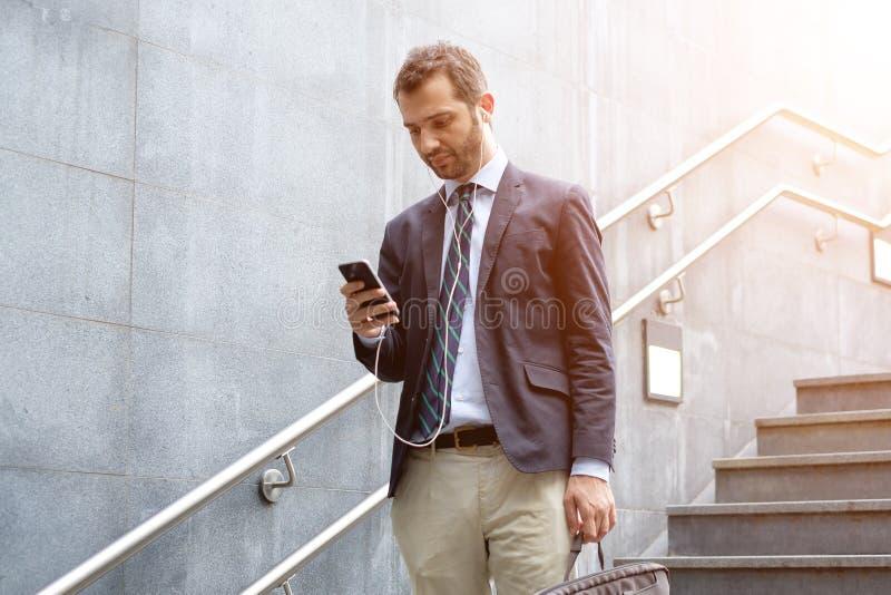 Homme d'affaires réussi regardant sur son smartphone dans le streptocoque de ville images libres de droits