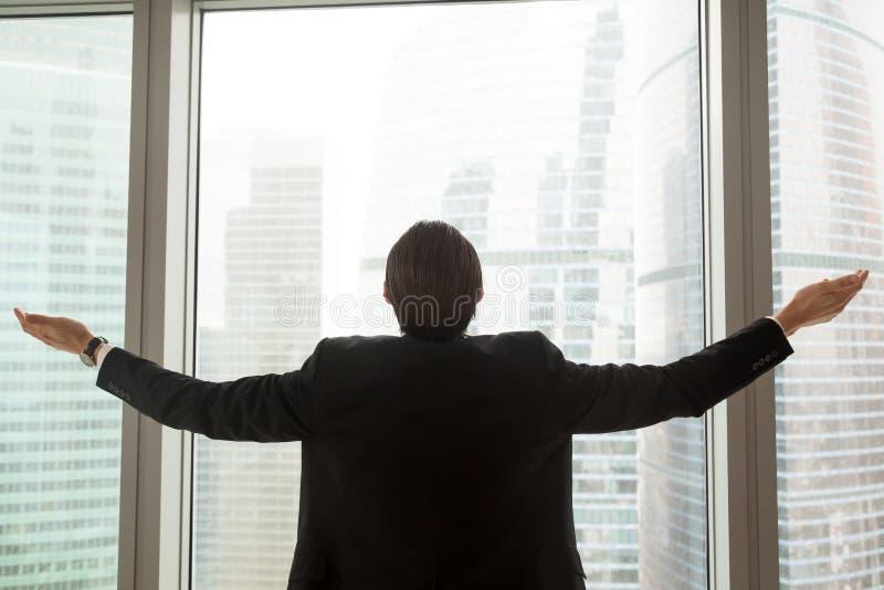 Homme d'affaires réussi tenant la fenêtre proche de bureau avec le wid de bras images stock