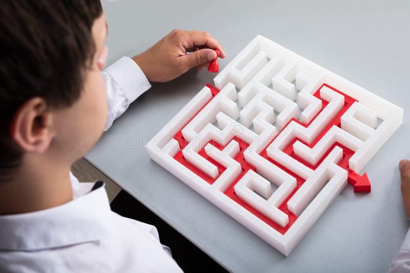 Homme d'affaires r?solvant le labyrinthe image stock